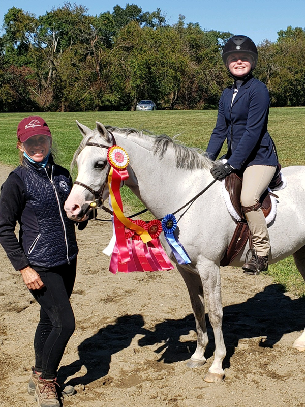 Leslie with young competitor and multiple placement ribbons